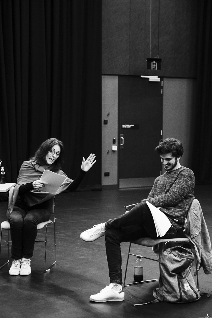 Dark haired woman and dark haired man rehearsing play on stage with scripts